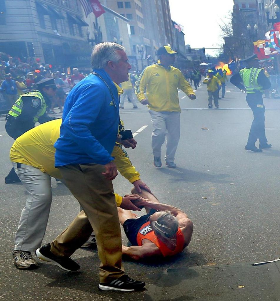 A Boston Marathon official helps a runner thrown to the ground. Photo by John Tlumacki, Boston Globe